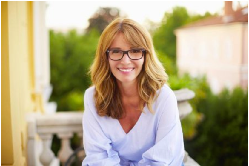 Middle-aged woman wearing glasses sitting outdoors creates the look of a smart, sophisticated, well-traveled woman.