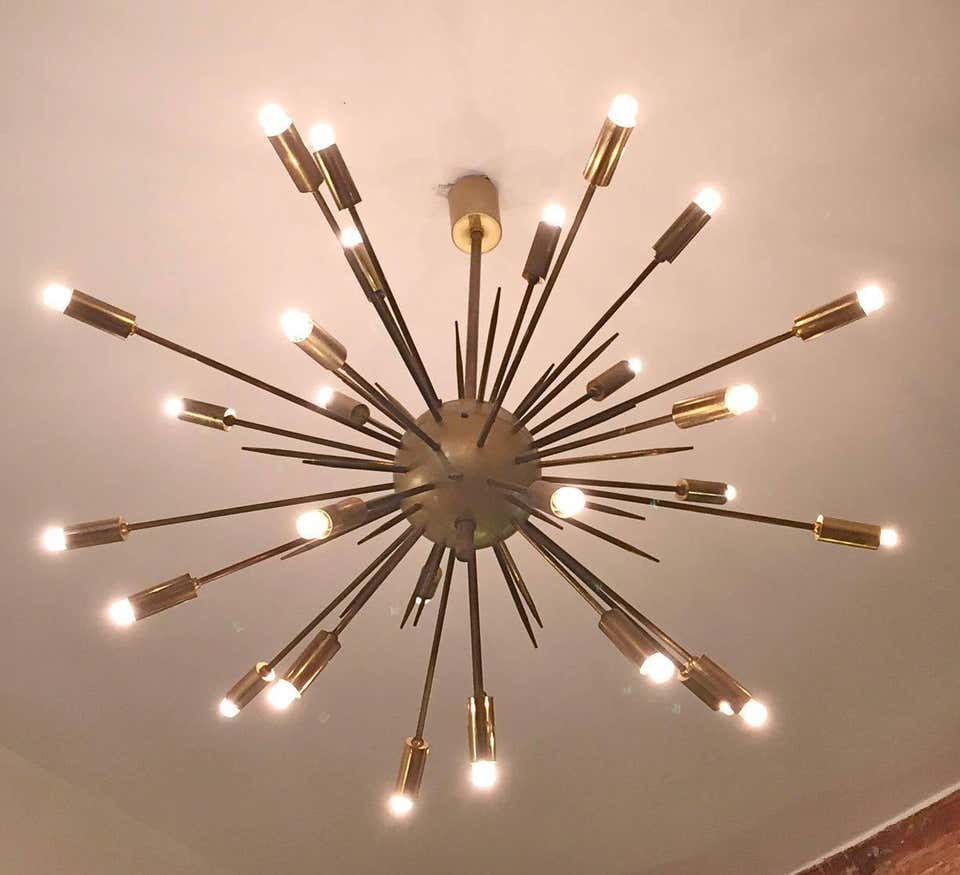 An original sputnik brass chandelier composed of 24 arms attached to a brass ball in the center which mimicked the Soviet satellite Sputnik 1.