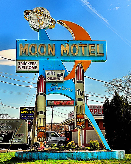 Motel sign in the U.S.A. that features a globe, a moon and two rockets.