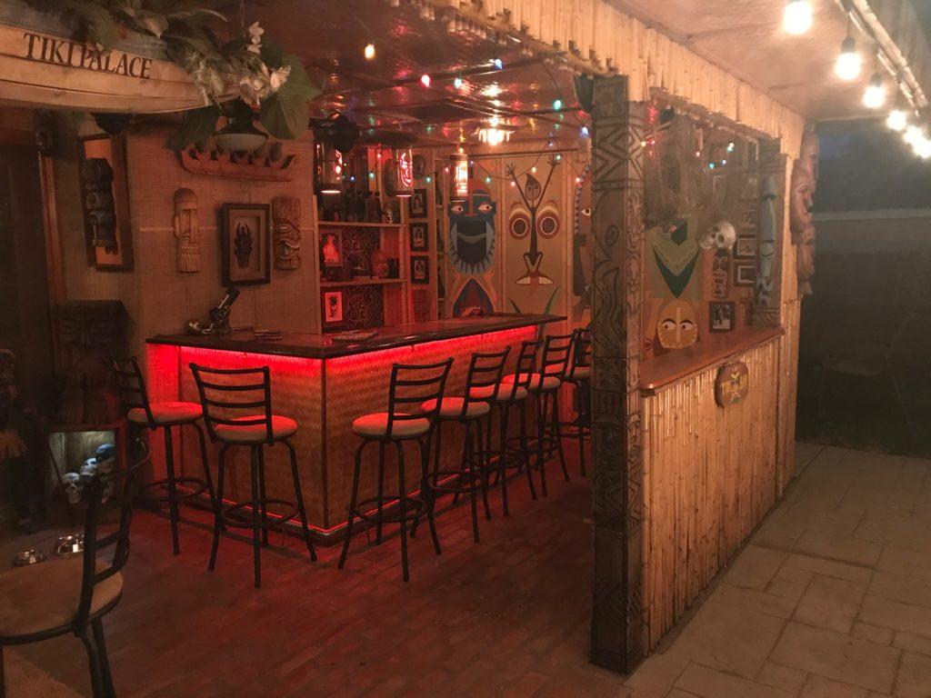 Home Tiki Bar made by enclosing a patio and covering wall in bamboo, Hawaiian mats, and Tiki decor.