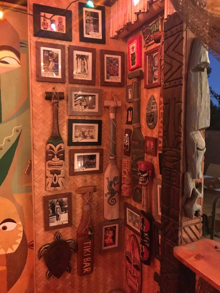 Historic photos from Hawaii, native masks, paddles, and wooden carvings for a Tiki decor.