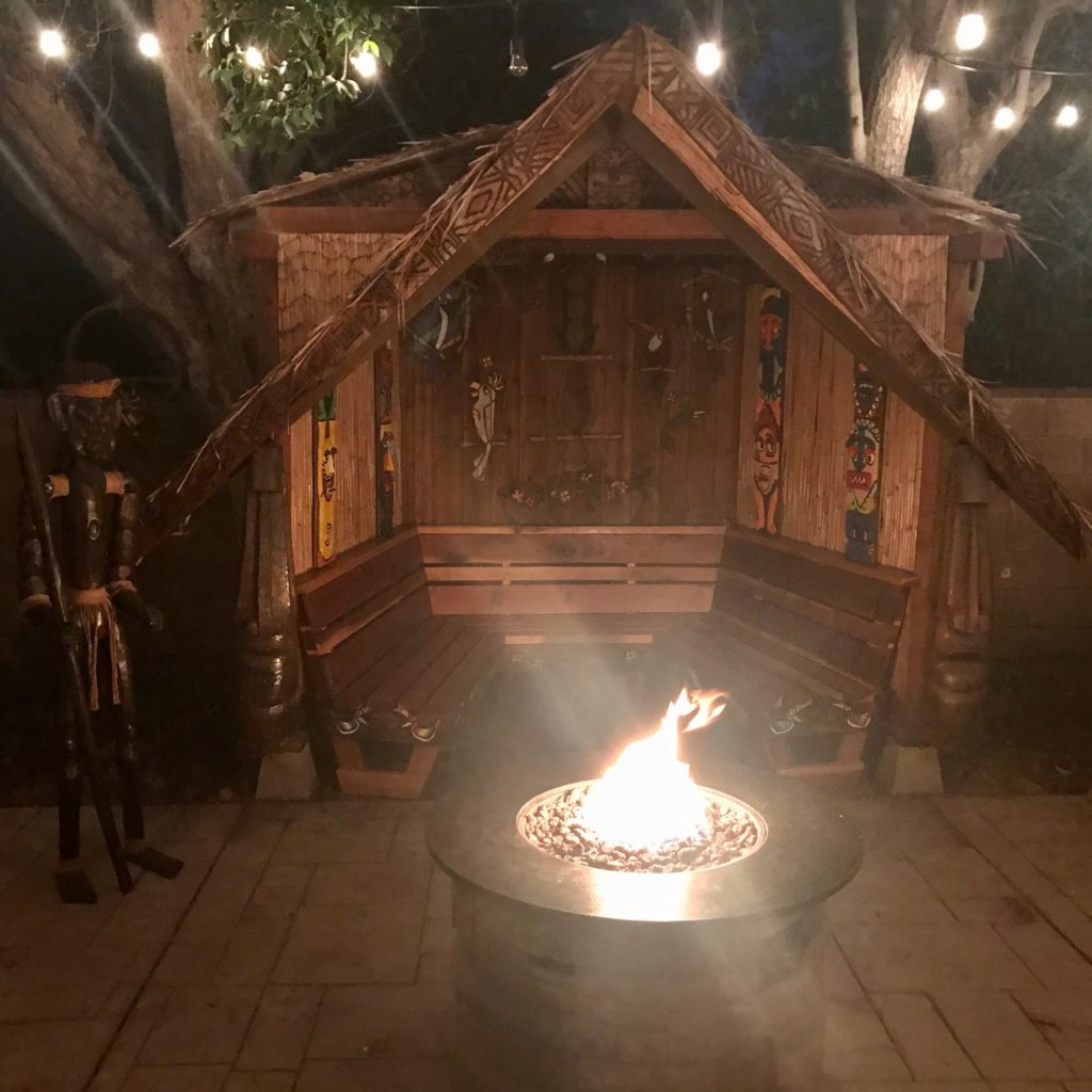 A-framed hut built in backyard with a fire pit and Tiki accents like carvings and masks.