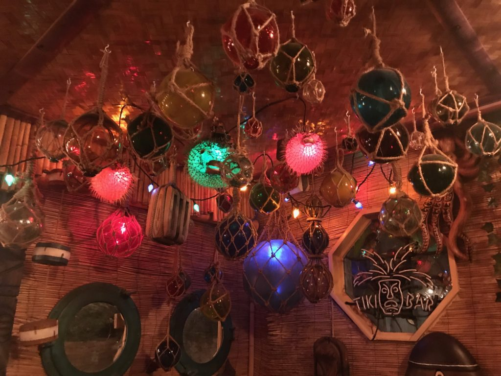 Japanese glass balls used as floats for fishing nets, puffer fish with lights, neon Tiki Bar sign