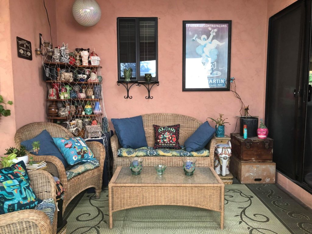 Patio with Tiki mugs in corner, wicker furniture and thematic pillows.