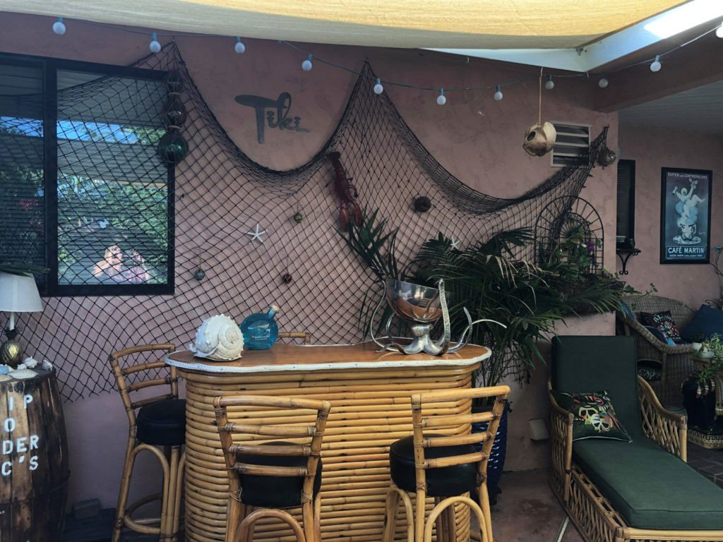 Rattan Tiki Bar with chairs. Fishing net on back wall and Trader Vic's barrel as an end table.