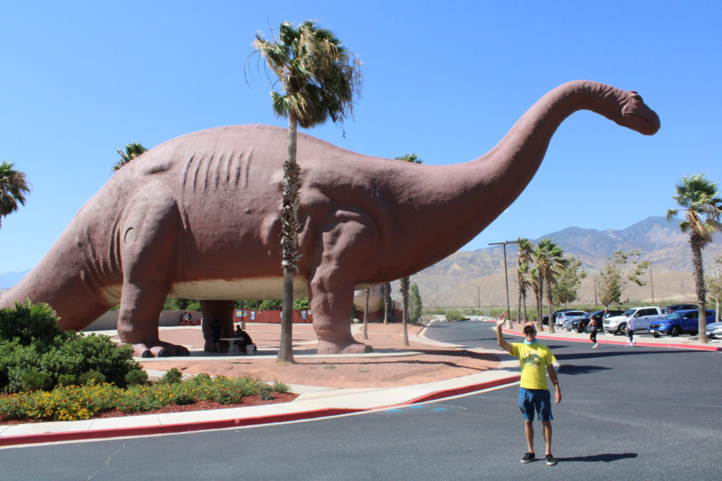 Dinny the Dinosaur with man and palm tree for scale