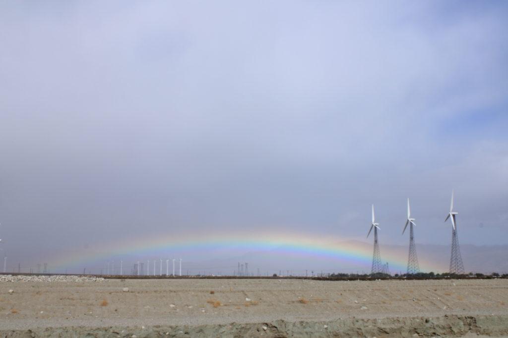 Rainbow ending at three wind turbines