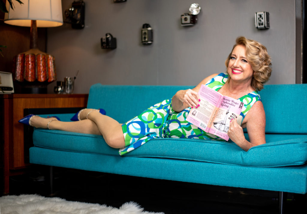 Author in retro dress, laying on midcentury couch and holding her book Bettie Page: Aphrodite Rising.