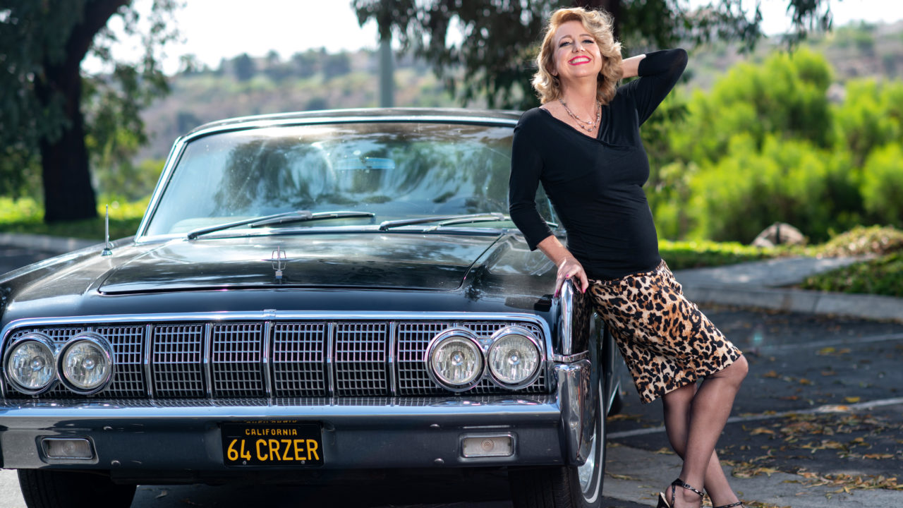 Author posing in front of classic car in black sweater and leopard print skirt