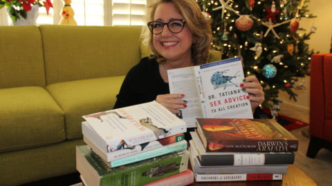 Author with stack of recommended books