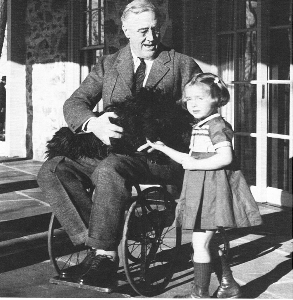 A rare photo showing FDR in his wheel chair. He has a dog on his lap and a child at his side.